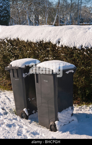 Two domestic waste bins awaiting collection during the winter - Stock Photo
