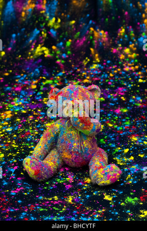 Teddy bear sat on a black cloth covered in coloured powder. Still life - Stock Photo