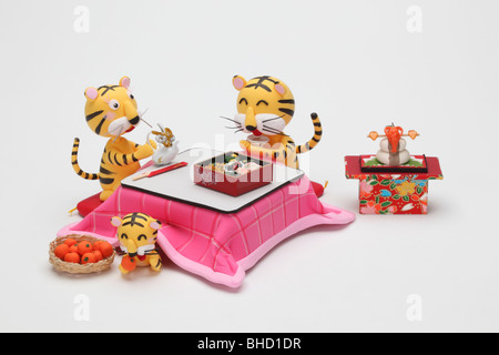 Tiger figurines eating New Year's dishes - Stock Photo