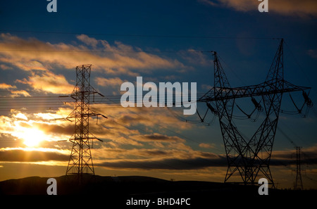 High voltage electical transmission power lines are silhouetted against a sunset - Stock Photo
