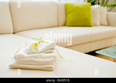 Folded towels with lily on sofa - Stock Photo
