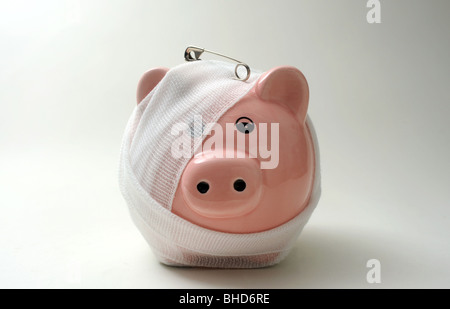 BANDAGED/INJURED PIGGYBANK WITH SAFETY PIN RE FINANCE LOANS CASH MONEY SAVINGS PIGGY BANK BANKS MORTGAGES INCOMES WAGES UK ETC Stock Photo