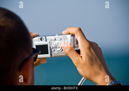 Taking pictures of sea with digital camera - Stock Photo
