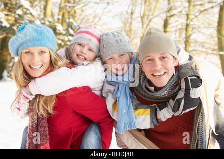 Family Having Fun Snowy Woodland - Stock Photo