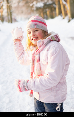 Girl About To Throw Snowball In Snowy Woodland - Stock Photo