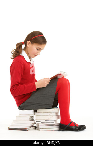 Female Student In Uniform Sitting On Pile Of Books Reading - Stock Photo