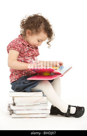 Young Girl Sitting On Pile Of Books Reading - Stock Photo