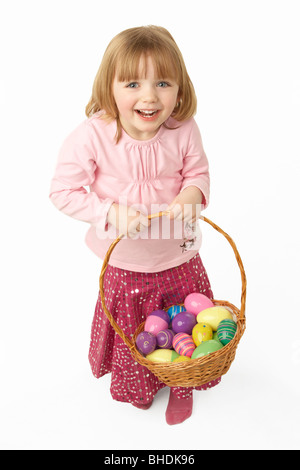 Young Girl Carrying Basket Filled With Easter Eggs - Stock Photo