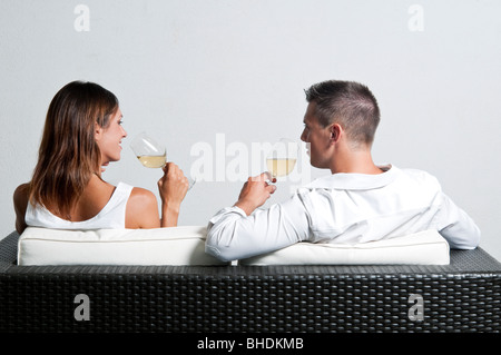 View of couple from the back sitting on couch drinking white wine - Stock Photo
