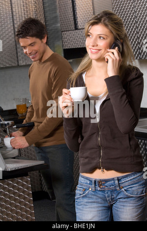 young woman using mobile phone and man making coffee - Stock Photo