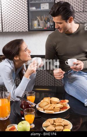 couple drinking coffee in kitchen, breakfast - Stock Photo
