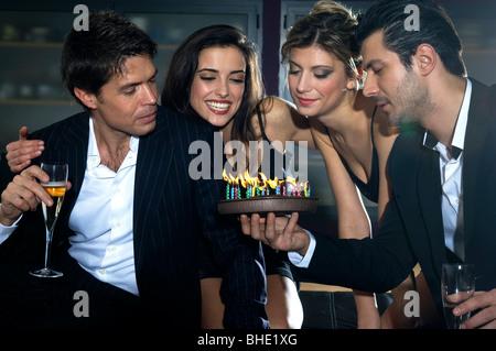young women and men celebrating birthday - Stock Photo