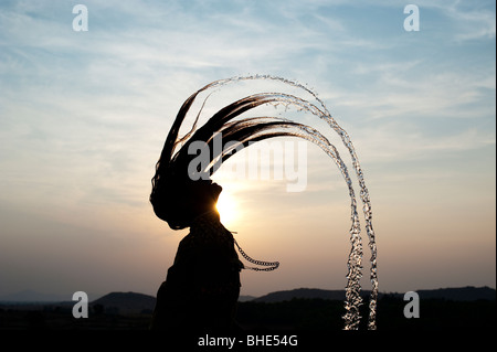 Indian girl throwing her wet hair back causing water spray silhouette. India - Stock Photo