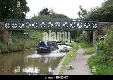 A canal barge or narrow boat on the Macclesfield canal going under a bridge just after coming out of a lock. - Stock Photo