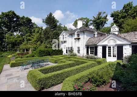 Bluestone patio with bushes in landscape design - Stock Photo