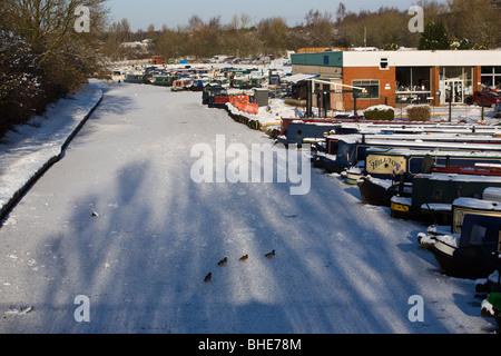 Narrow boats on frozen Leeds and Liverpool canal at White Bear Marina in Adlington - Stock Photo