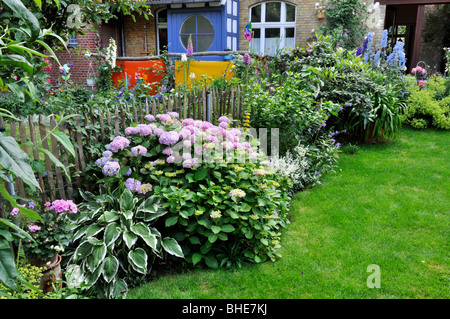 Terraced border of shrubs in garden and bungalow Stock Photo
