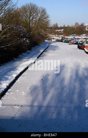Narrow boats on frozen Leeds and Liverpool canal at the White Bear Marina in Adlington - Stock Photo