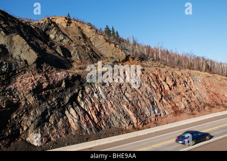 A road cut along highway 61 in northern Minnesota through ancient volcanic rock near Lake Superior. - Stock Photo