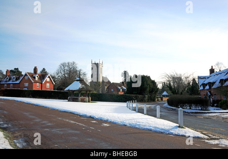 The village green and pump with the Church of SS Fabian and Sebastian in winter at Woodbastwick, Norfolk, United - Stock Photo