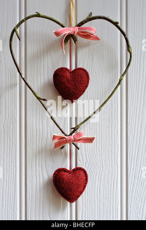 Decorative heart made of birch twigs tied with woven red and white ribbon with hanging red felt hearts - Stock Photo