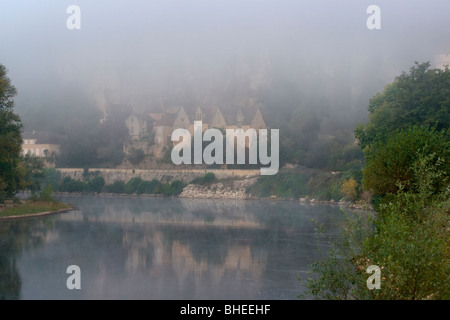 Early-morning mists and fog shrouds a mysterious chateau, reflected in the Dordogne River, la Roque Gageac, France, - Stock Photo