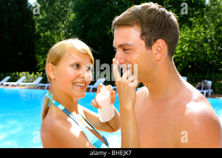 woman applying sunscreen to man's nose at poolside - Stock Photo