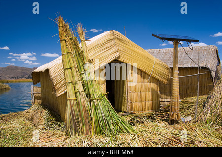 Huts made from totora reeds and a solar panel, blending old and modern technology. Uros Islands, Lake Titicaca,Peru - Stock Photo