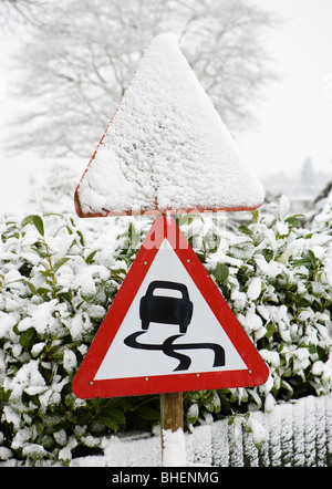 Danger, slippery road sign in winter. - Stock Photo