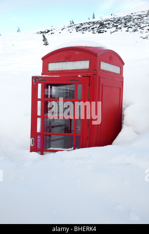 Deep snow almost buries a traditional red telephone box on the mountains in Aviemore, Cairgorms, Scotland. - Stock Photo