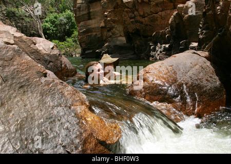 A couple enjoys the water of a rock pool in the escarpment of Nitmiluk National Park Arnhem Land Australia - Stock Photo
