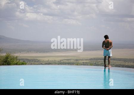 Bather by outdoor swimming pool at the Serena Manyara Lodge, Tanzania - Stock Photo