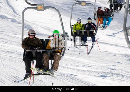 young skiers on ski chair lift, kitzbuhel, austria - Stock Photo