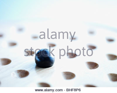 Marble on Chinese checkers board - Stock Photo