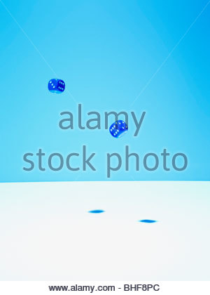 Blue dice in mid-air - Stock Photo