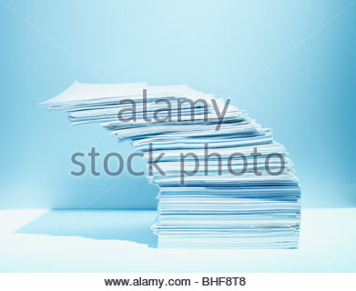Stack of paper piled precariously - Stock Photo