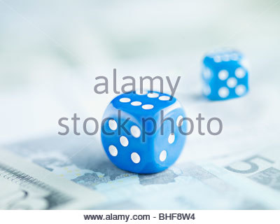 Two blue dice on pile of euro notes - Stock Photo