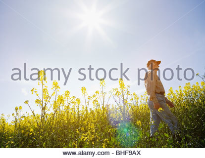 Farmer walking through field - Stock Photo