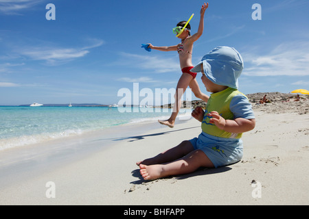 Children playing on the beach, Playa de Llevant, Formentera, Balearic Islands, Spain - Stock Photo