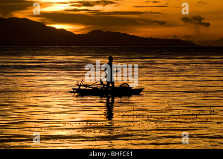 Man standing paddling in a canoo at sunset, New Britain, Papua New Guinea, Oceania - Stock Photo
