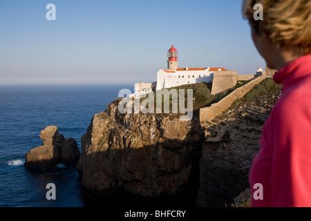 Young woman at the lighthouse at Cape Cabo de Sao Vicente, Atlantic Ocean, MR, Sagres, Algarve, Portugal - Stock Photo