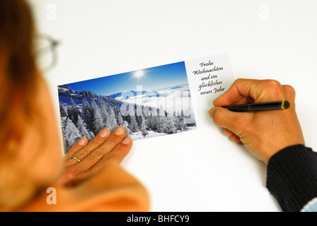 Woman writing Christmas card with winter subject - Stock Photo
