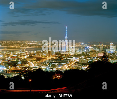 View at the illuminated Central Business District with Sky Tower at night, Auckland, North Island, New Zealand - Stock Photo