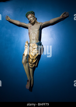 religious art sad looking Jesus hanging on a blue wall in a museum in Luik, Belgium - Stock Photo