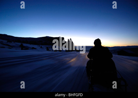 Man on a skidoo in the evening light, Seiser Alm, Schlern, South Tyrol, Italy - Stock Photo