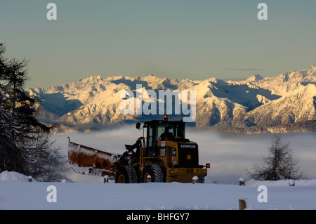 Snow plough clearing snow in the morning light, Seiser Alm, South Tyrol, Italy - Stock Photo