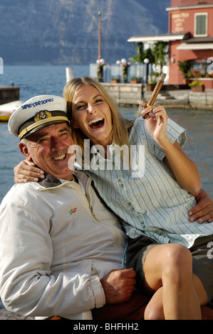 Laughing woman holding a cigar sitting on the lap of a man wearing a captain's cap, Garda lake, Italy, Euorpe - Stock Photo