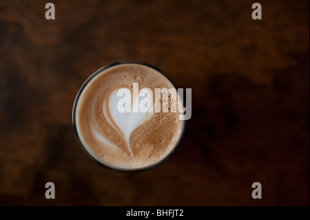 A love heart drawn in 'latte art' on top of a tall cafe latte coffee. - Stock Photo