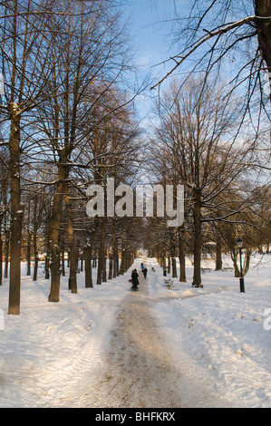 People walking through Humlegården park in Stockholm on a cold winter's day. - Stock Photo