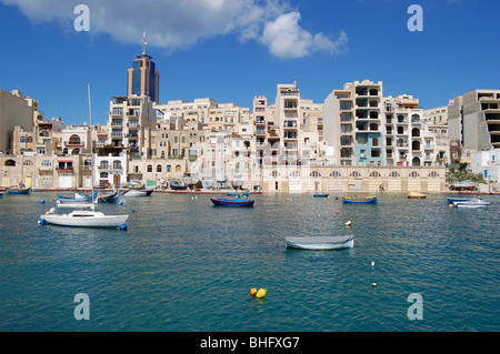 A view of St. Julians bay with buildings being constructed in the background overlooked by the Hilton hotel. - Stock Photo
